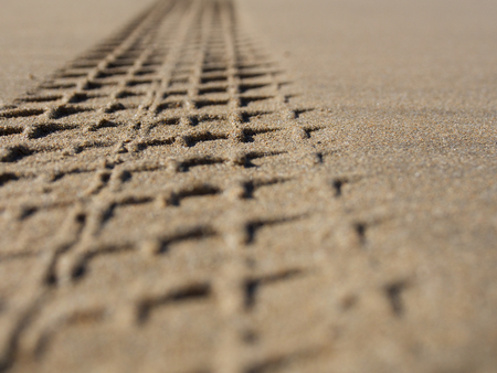 four wheel drive: selective focus of a tread mark in sand