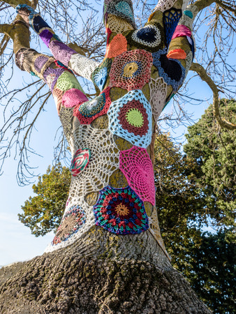 Example of colorful yarn bombing around a tree in an Australian rural farm Stock Photo
