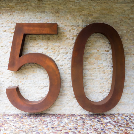 50 number: the number fifty 50 sign in rusty metal against a stone wall