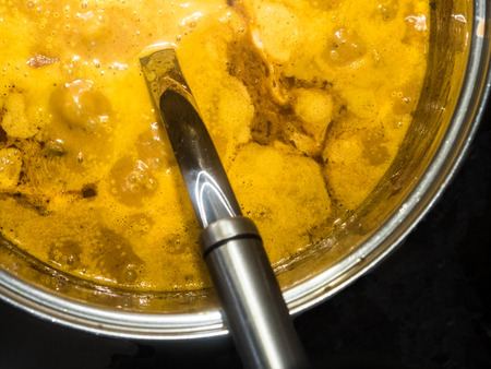 close up of a yellow bubbling curry cooking on a stove top Stock Photo