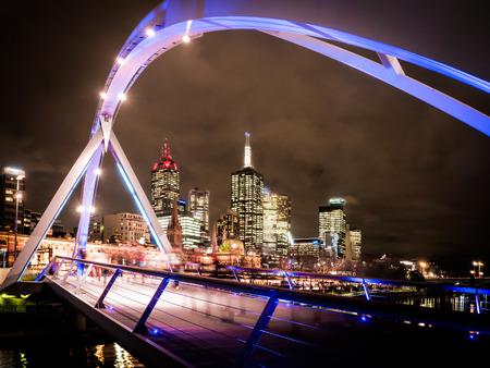 melbourne city australia at night looking down the yarra river looking across a foot bridge