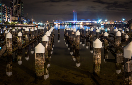 Looking over an old pier towards the Bolte bride in the docklands district in Melbourne