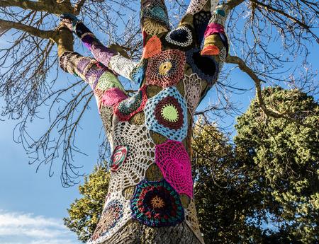 Example of colorful yarn bombing around a tree in an Australian rural farm Фото со стока