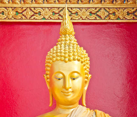 Golden Lord Buddha close up over the red wall Stock Photo