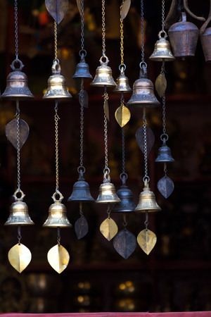 Chimes hanging in the window Decorative bells hang on the window behind with bokeh background The traditional wind bell fluttering in tropical wind in Nepal temple and house.