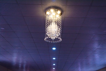 Decorative ceiling light with bare walls and copy space