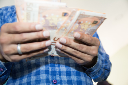 Male hands counting large amount of euro currency cash banknotes, low view