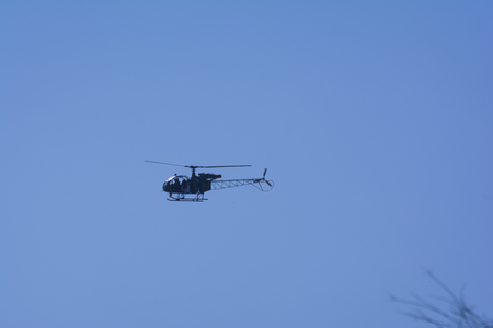 A small helicopter flying in the sky