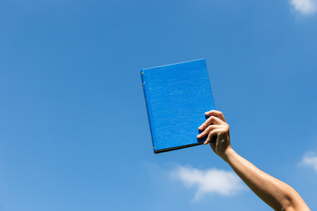 book holded by hand in the sky photo