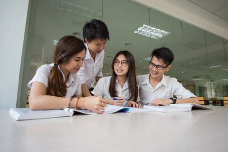 revision book: Asian student student discuss in library of university