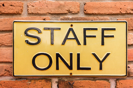 license plate: staff only on yellow license plate on red brick wall Stock Photo