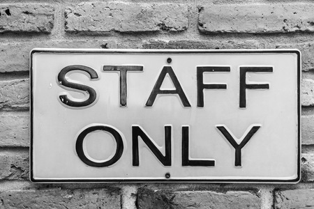 staff only: staff only on yellow license plate on red brick wall Stock Photo