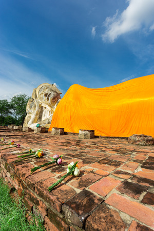 wat pho: beautiful lotus flower with candle in front of the Big reclining buddha statue with blue sky,Ayuthaya Thailand Stock Photo