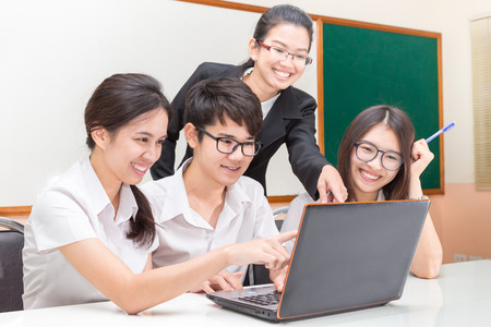 hispanic students: Asian student and teacher in classroom Stock Photo