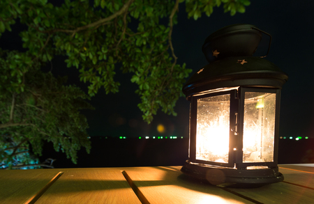 lamplight: candle lamp on the table with night sea view in Thailand
