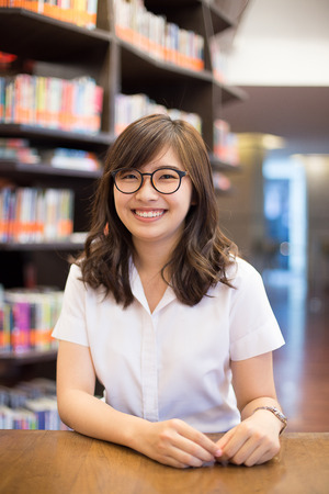 junior student: Asian student in library of university Stock Photo