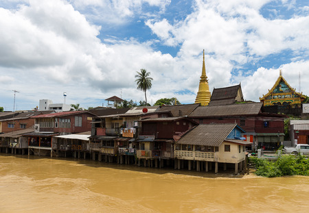 hometown: gold buddha temple behind the urban waterfront hometown in Thailand