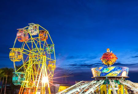 maching: ferris wheel and gravity maching in movable amusement park at sunset time in Thailand