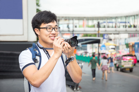 Smiling and handsome young asian travel with backpack and camera travel in Bangkok city Thailand