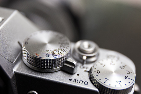 shutter speed and exposure control dial, button, on silver modern mirrorless camera Banco de Imagens