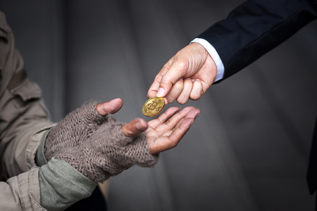 business man give, donate, his gold bitcoin to homeless man in downtown of business zone Stock Photo