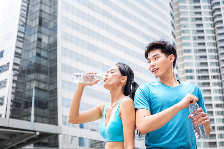man and woman, couple of love, drinking fresh water after running in the city, downtown of business zone 스톡 콘텐츠