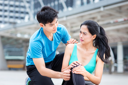 running injury, man help sport girl from  ankle hurt accident from playing sport in the city 스톡 콘텐츠