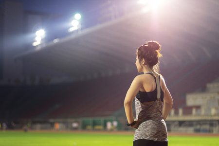 young female athlete stretching on grass in football stadium 스톡 콘텐츠