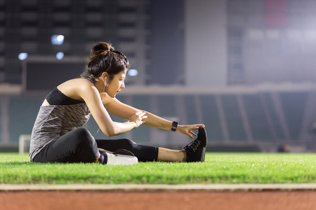 young female athlete stretching before running on grass in football stadium at night