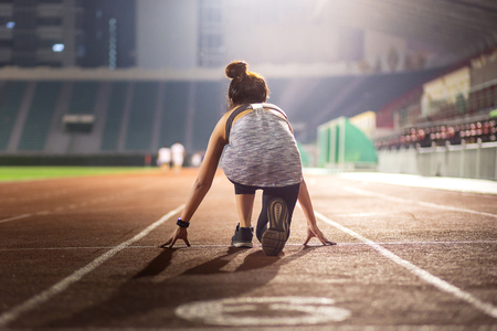 Happy young female athlete set at a starting position for running in stadium at night 스톡 콘텐츠