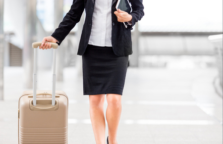 female manager hold her luggage and tablet in business zone in order to go to terminal at airport for a business travel trip on holiday