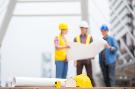 house, home, paper plan or blueprint, and other engineer tools with background of success engineer team discuss about work in the business zone of city