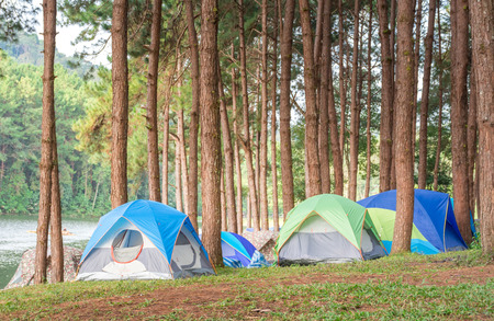 colorful tent of tourism, who travel for hiking and adventure in forest with view of lake on high mountain in Thailand during long vacation