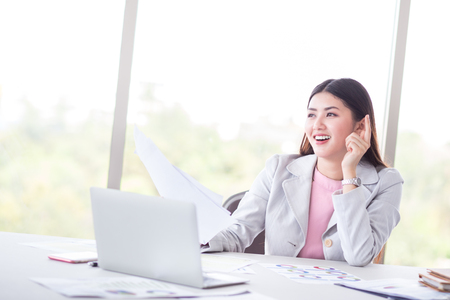 portrait of happy and smile success business woman with laptop, computer, and document on working desk. Smiling after finish her business work by using smart technology, laptop, to analyze business gr