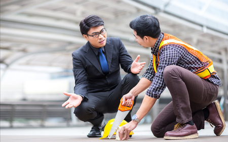 misunderstand teamwork between manager business man and young engineer discuss during project meeting at industrial construction site about the plan and bluepring mistake of home and house concept, wi