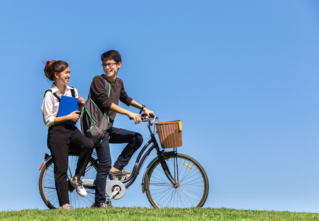 young asian students ride a bicycle with book in university with nature background