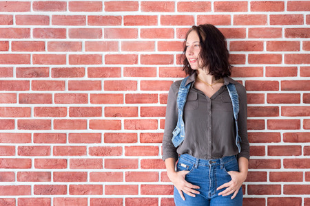 Happy russian girl wear jean as her lifestyle in holiday for travel and shopping with copyspace of red brick wall background 스톡 콘텐츠