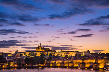 View of Charles bridge over Vltava river, St. Vitus Cathedral castle, St. Nicholas Chruch where is the most popular landmark for travel in Prague or Praha, in Czech Republic, Europe at sunset time