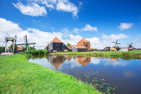 windmill and view of famous place from tourist Zaanse Schans farm and industry in Amsterdam, Netherlands with clear blue sky and reflection on water also moment of cow, duck, bird, and other animals i 스톡 콘텐츠