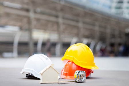 house model, measuring tape, safety helmet, and construction or engineer equipment with copy space of business zone in city or downtown. Concept of engineer, business, construction, and safety