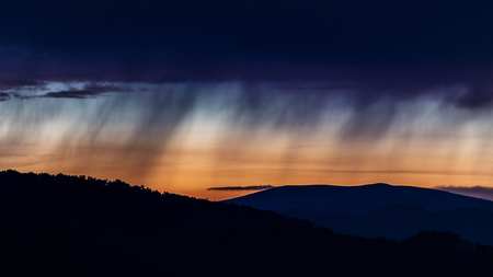 smooth of silhouette rain water on sky and cloudy storm at sunset time over the layer of mountain in national park and copy space on sunset sky
