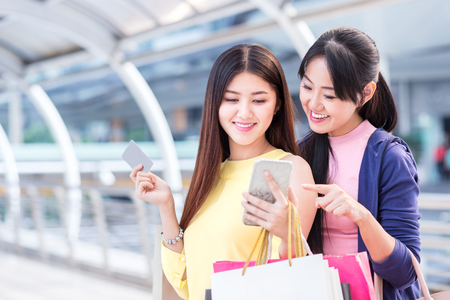 happy beautiful young woman enjoy shopping and hold paper shopping bag and mobile phone in the city with summer sale in shop at department store in center of downtown or business zone