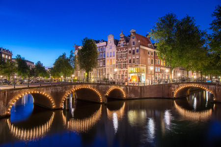 Apartment along Keizersgracht canal in Amsterdam city at Netherlands with reflection on water at sunset time, famous canal for transportation by boat and car on the street and bridge over river