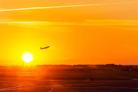 Silhouette of aeroplane, plane, take off on air at sunset time with all passenger on board for travel and for business at airport, with copy space of sunset sky, concept of travel, and transportation