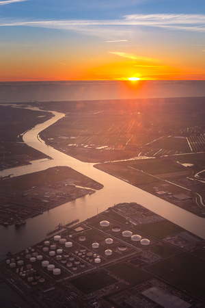Aerial view of oil and gas tank farm in petrochemical and petroleum industrial close to river and connect to sea, ocean, for transportation at sunset time from window seat on airplane 에디토리얼