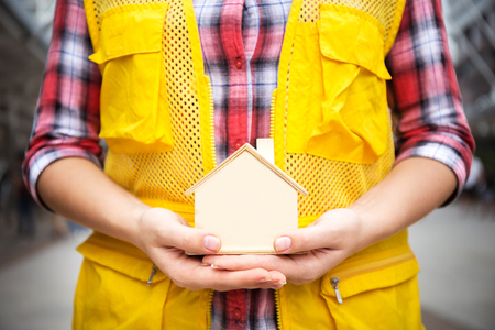 House, home, model which made from wood in hand of young female engineer, wearing safety helmet and suit in concept of hope or dream for living with copy space of blur background of skyline in downtow 스톡 콘텐츠