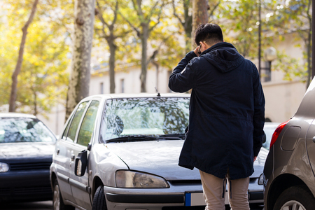 serious man stand in fron of his broken car park on road in Paris, France with autumn, color leave