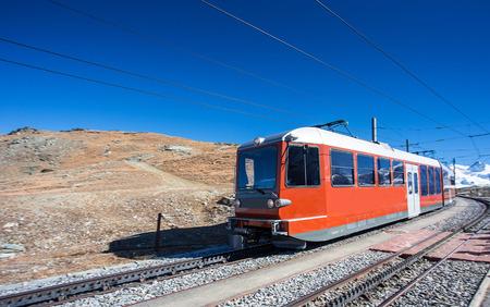 red tram or train on rail transportation to Matterhorn, popula Alps peak at Zermatt, Switzerland, Europe with clear blue sky 스톡 콘텐츠