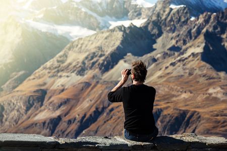 fashion tourist man look nature view of snow and dry layer of mountain through binoculars on top of view point on mountain in Switzerland