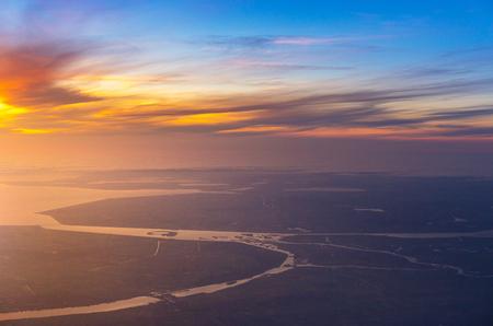 Hermosa puesta de sol con vista aérea del mar y el río desde el avión, avión, asiento de ventana sobre Holanda, Europa